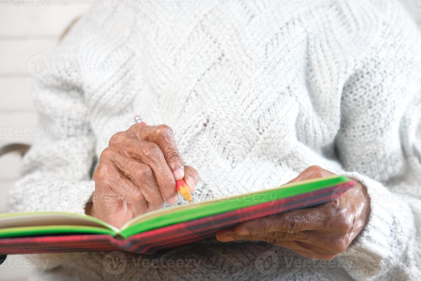 gammal kvinna som skriver i en anteckningsbok foto