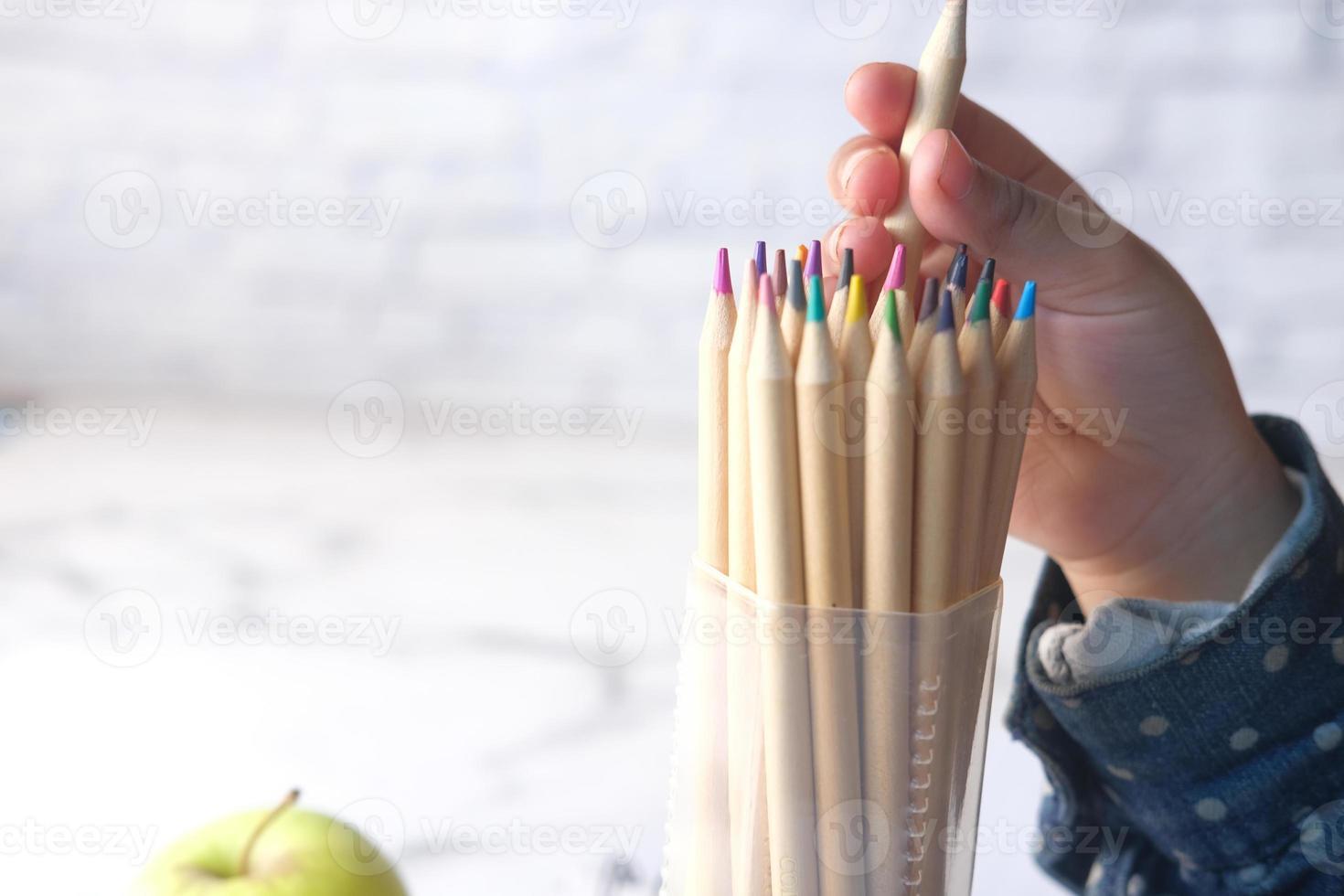 närbild av ett barns hand som plockar färgpennor foto