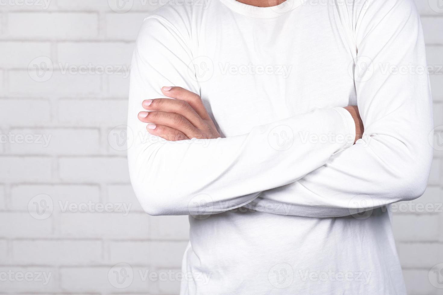 man står med korsade armar på neutral bakgrund foto