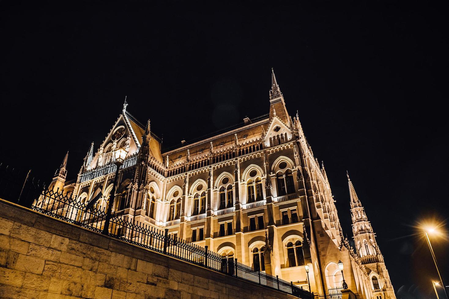 det ungerska parlamentet i Budapest på Donau i nattlamporna på gatlyktorna foto