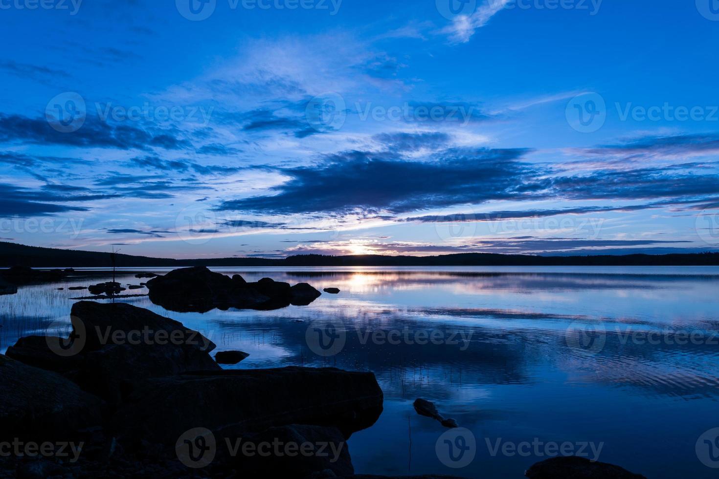 vacker sommarsolnedgång vid en sjö i sverige foto