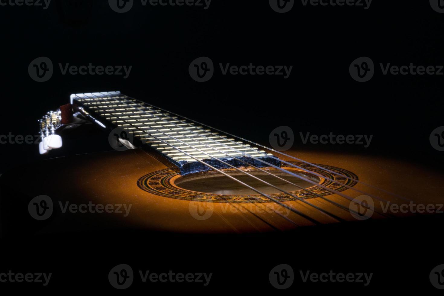 ovanlig utsikt över en akustisk gitarr upplyst och lyser i mörkret foto