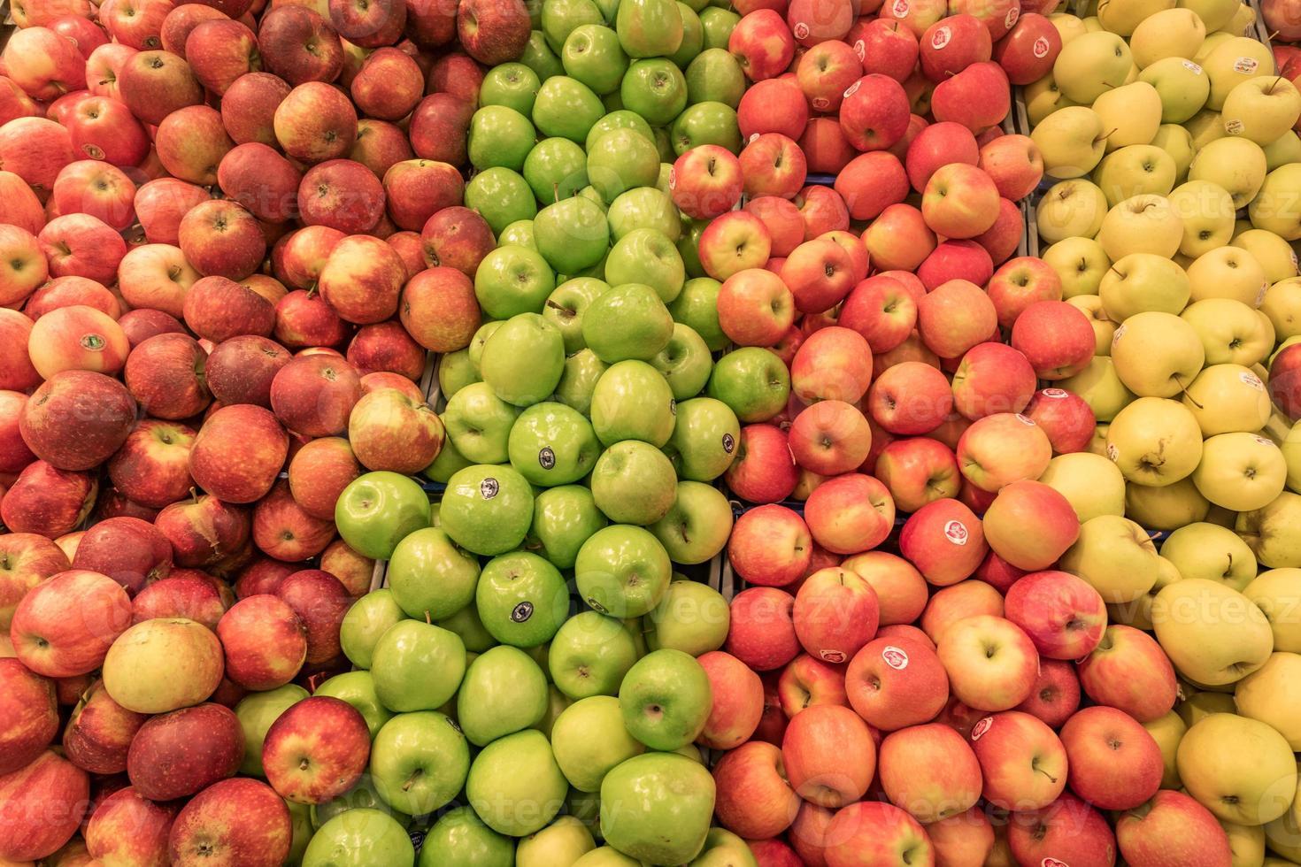 disk fylld med färgglada äpplen i olika färger foto