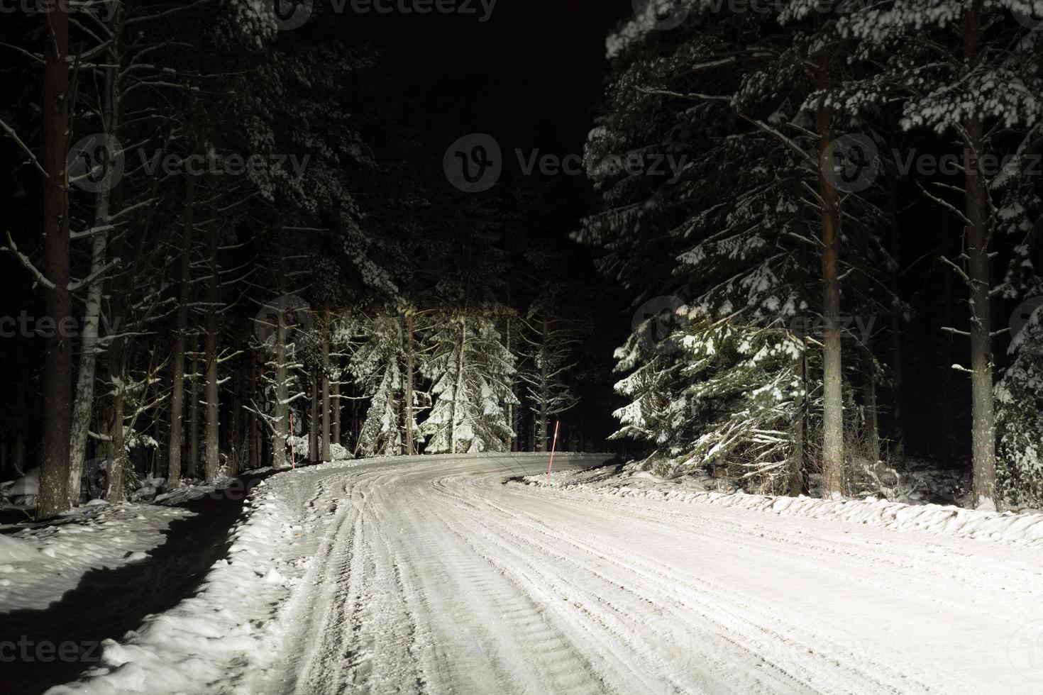 utsikt över en hal vinterväg med helljusstrålkastare på natten foto