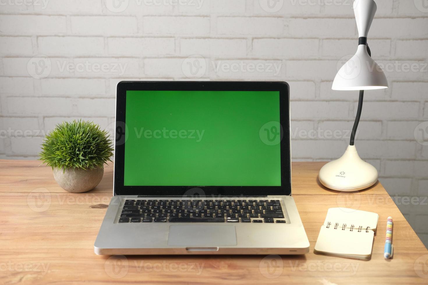 bärbar dator med grön skärm vid skrivbordet foto