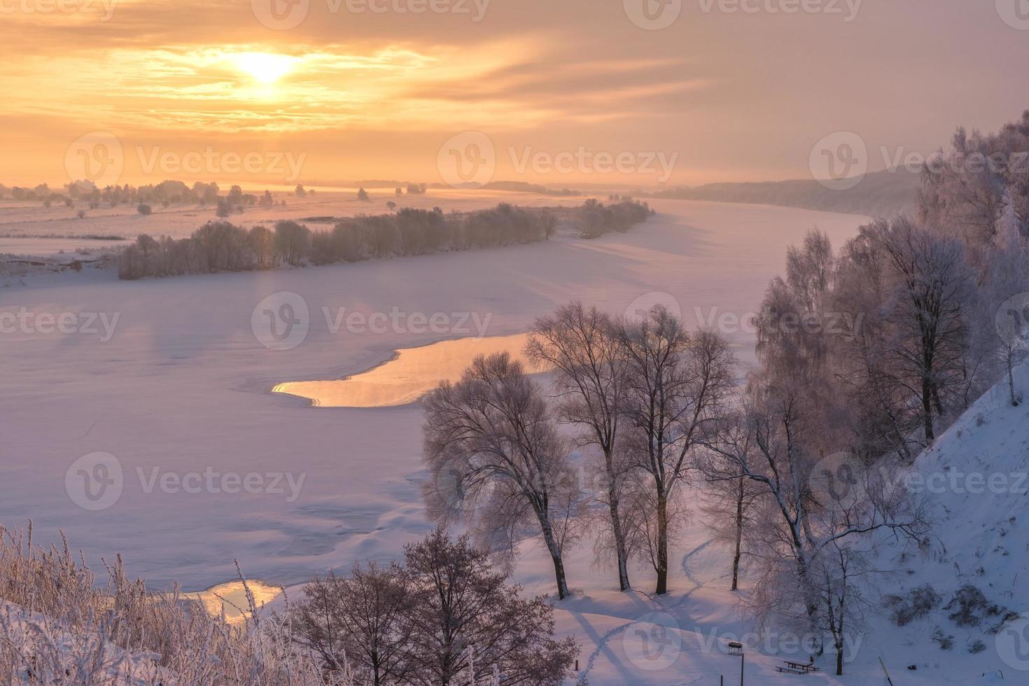 vackert vinterlandskap med soluppgång över floden foto