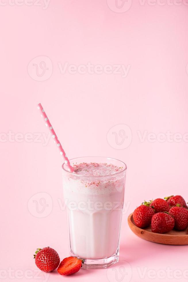 färsk milkshake med jordgubbar på rosa bakgrund foto