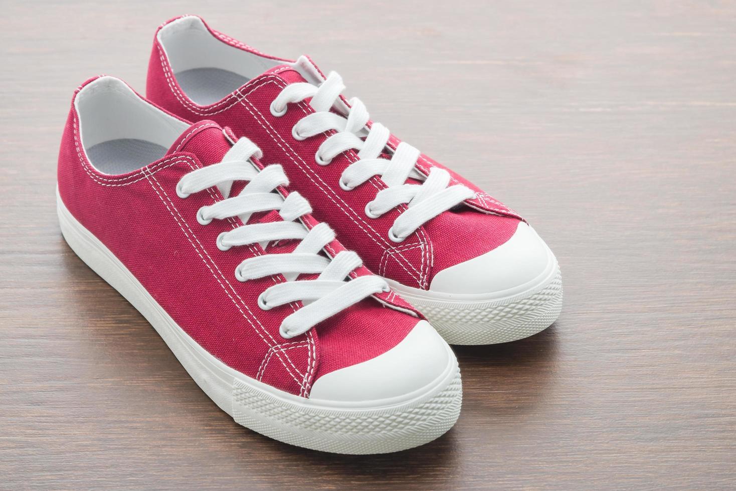 röda skor på träbakgrund foto