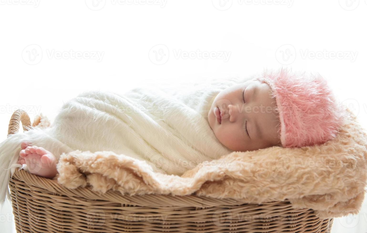 nyfött behandla som ett barn sova i en korg på vit bakgrund foto
