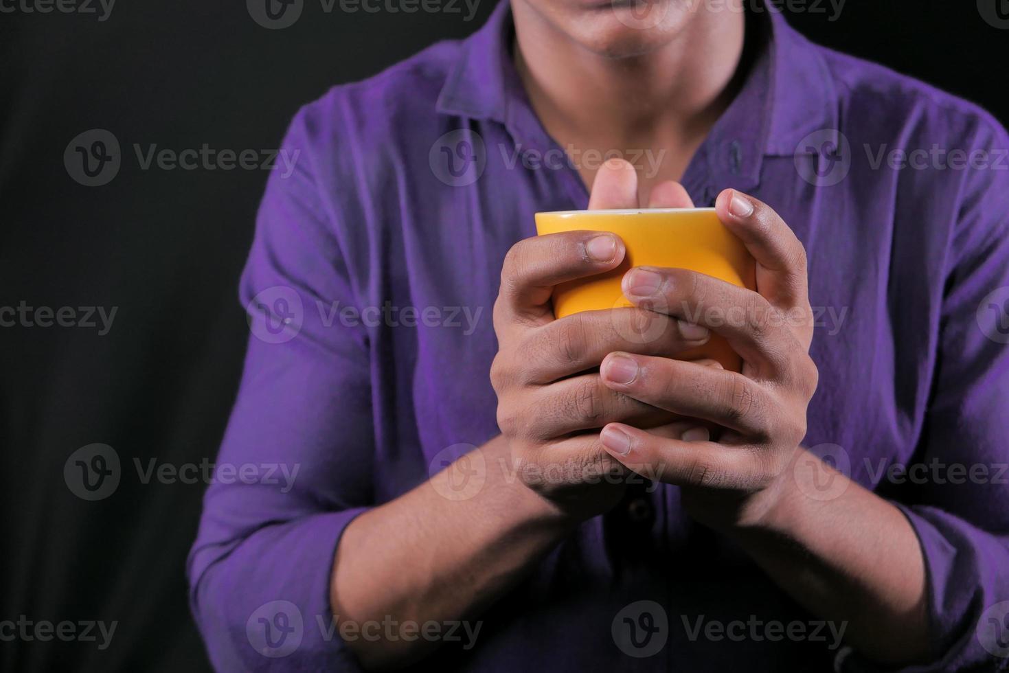 närbild av mannen som rymmer den gula mugg foto