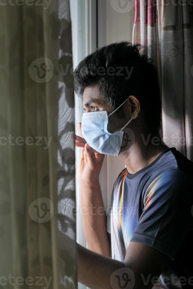 man som bär en mask som ser ut genom fönstret foto
