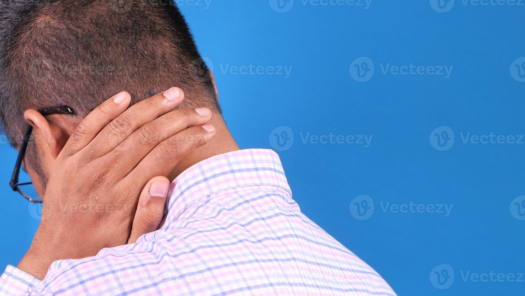 man som håller nacken i smärta bakifrån foto