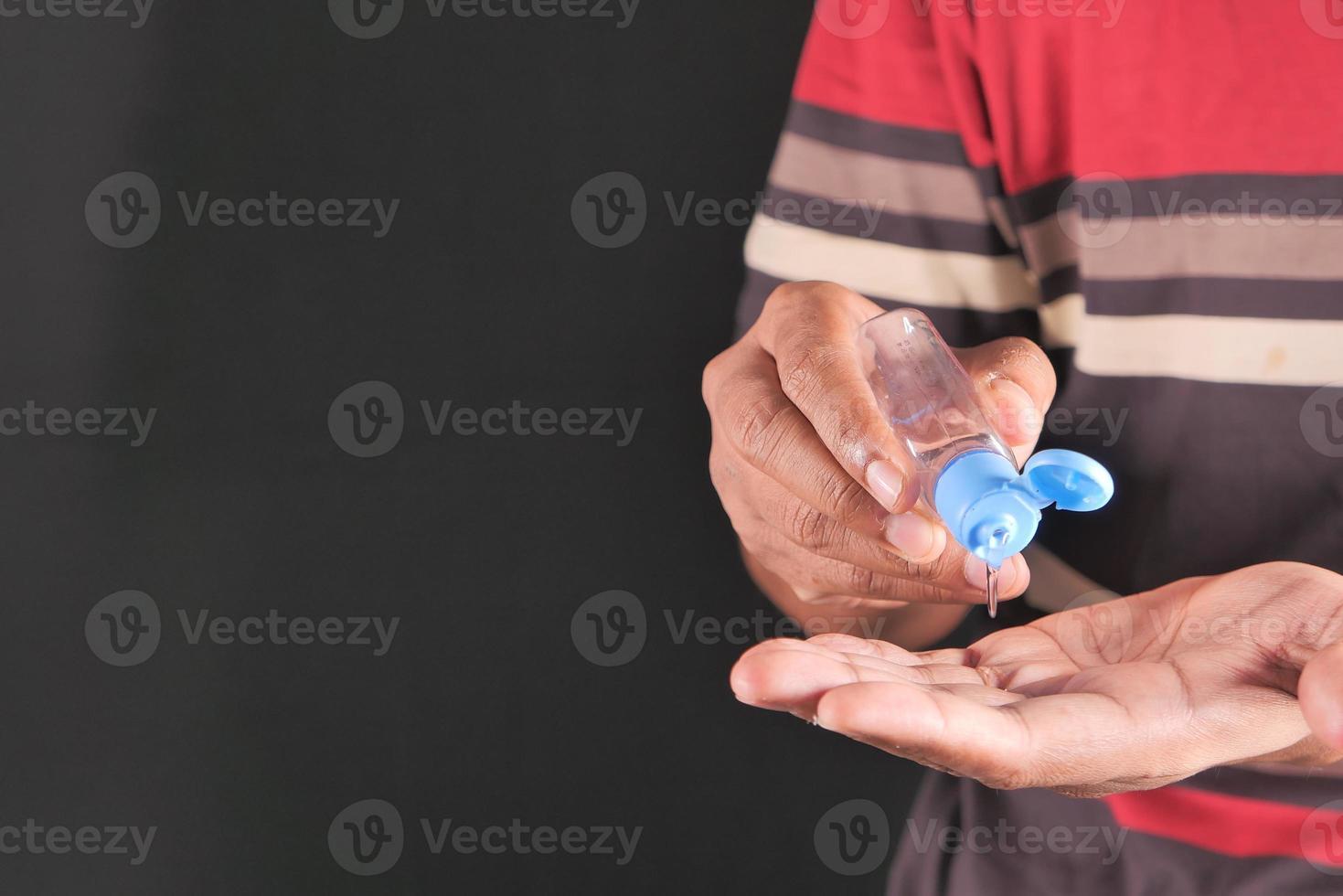 ung man använder desinfektionsgel foto