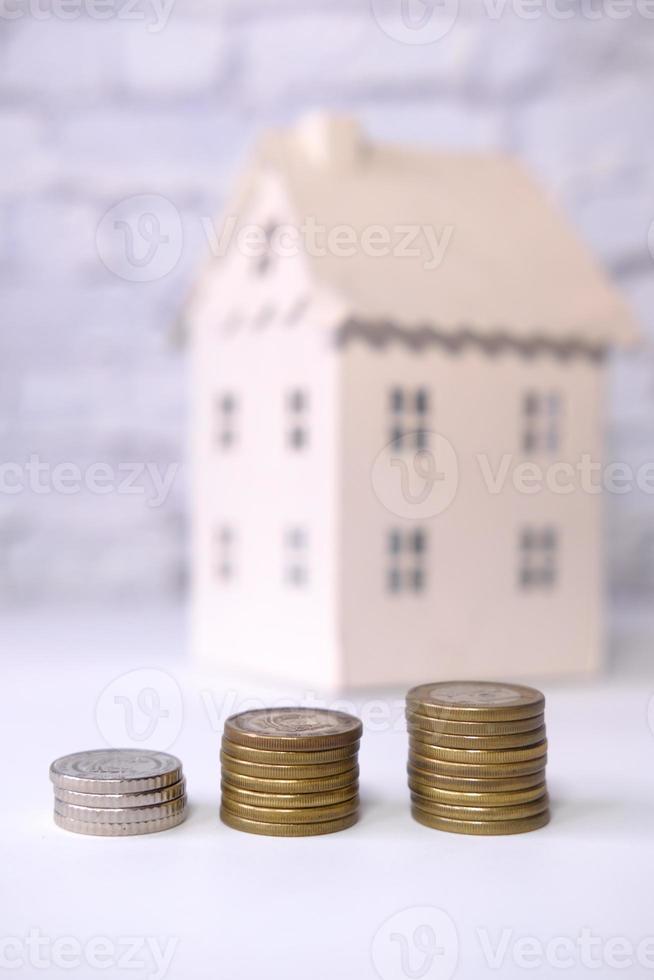 bunt med mynt och modellhem i bakgrunden foto