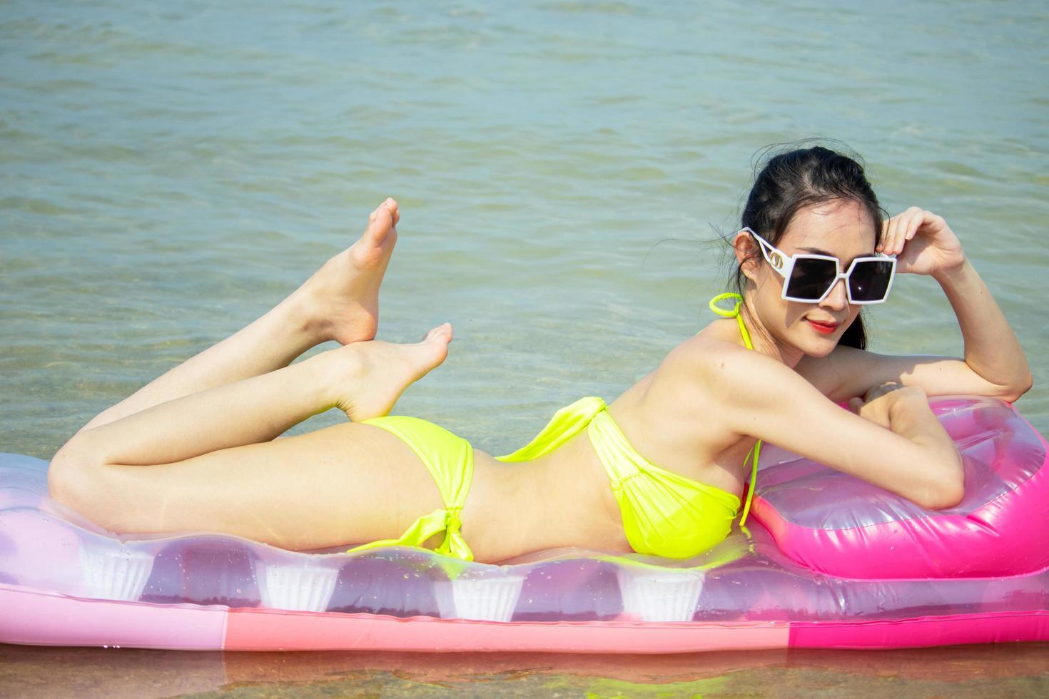 vacker asiatisk kvinna glad och avslappnad på en sommarsemester foto