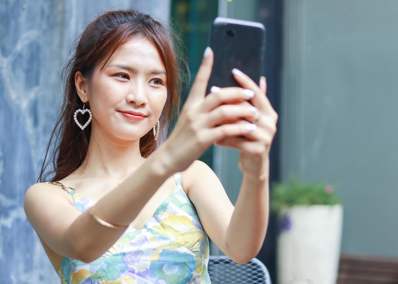 vacker asiatisk kvinna som gärna använder en smartphone för att ta selfies hemma foto