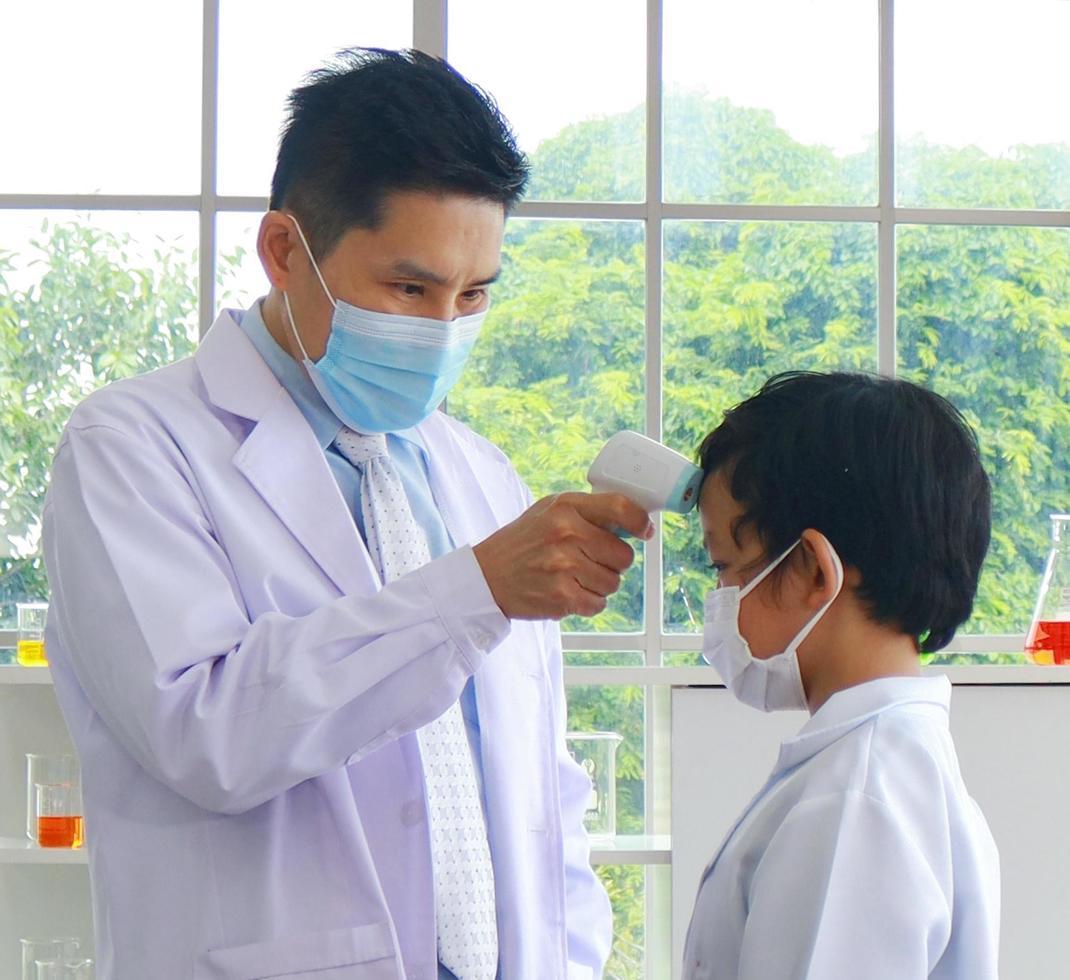 lärare använder en infraröd panntermometer för att kontrollera temperaturen hos en manlig elev innan de går till lektionen foto