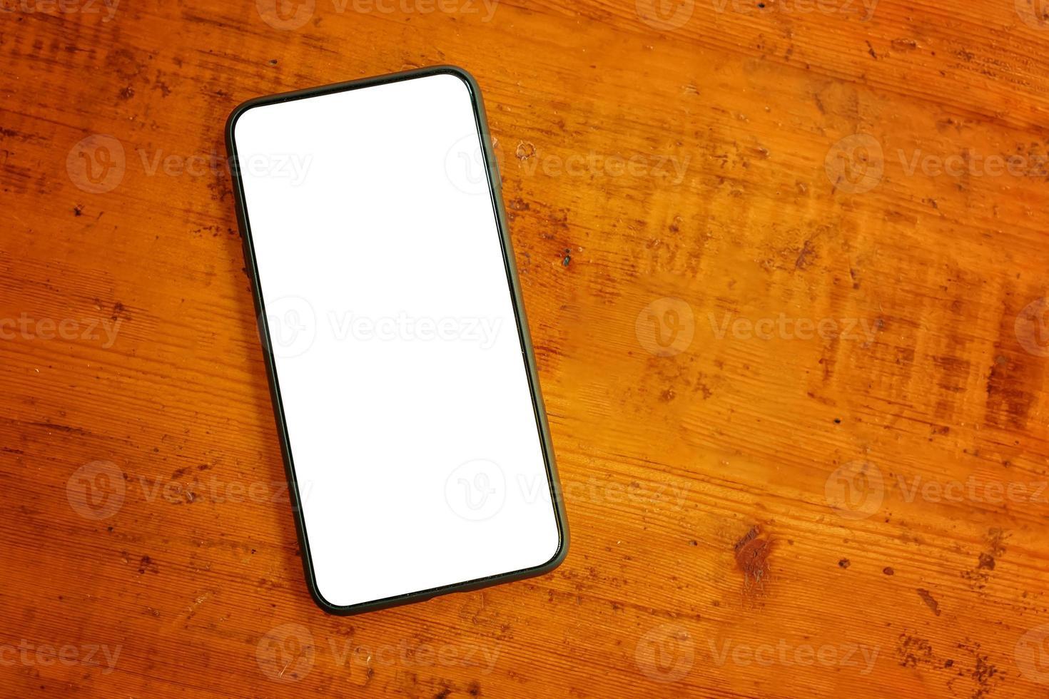 platt låg av mobiltelefon på träbord foto