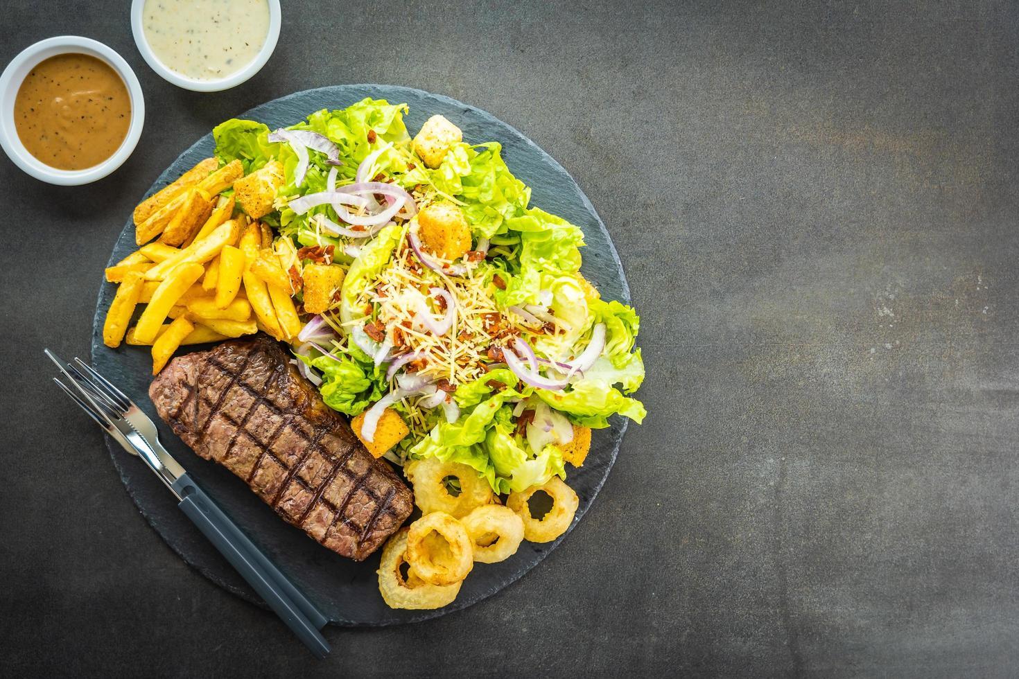 grillad nötköttbiff med pommes frites lökring med sås och färsk grönsak foto