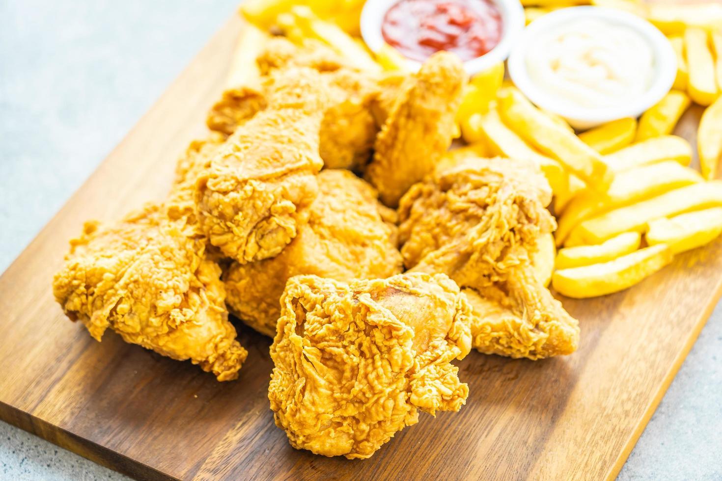 stekt kycklingvingar med pommes frites och tomat eller ketchup och majonnäs sås foto