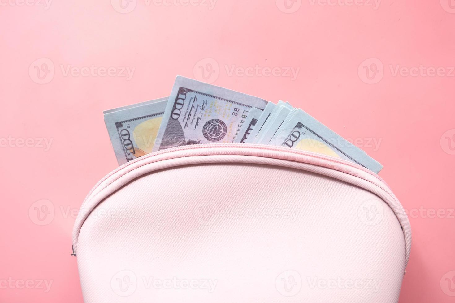 närbild av kontanter i plånbok på rosa bakgrund foto