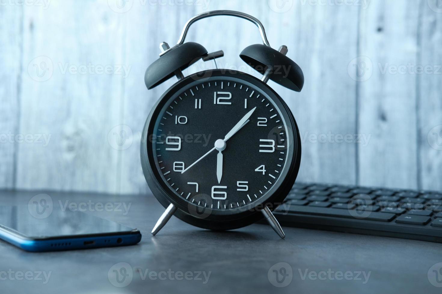 svart väckarklocka på skrivbordet foto