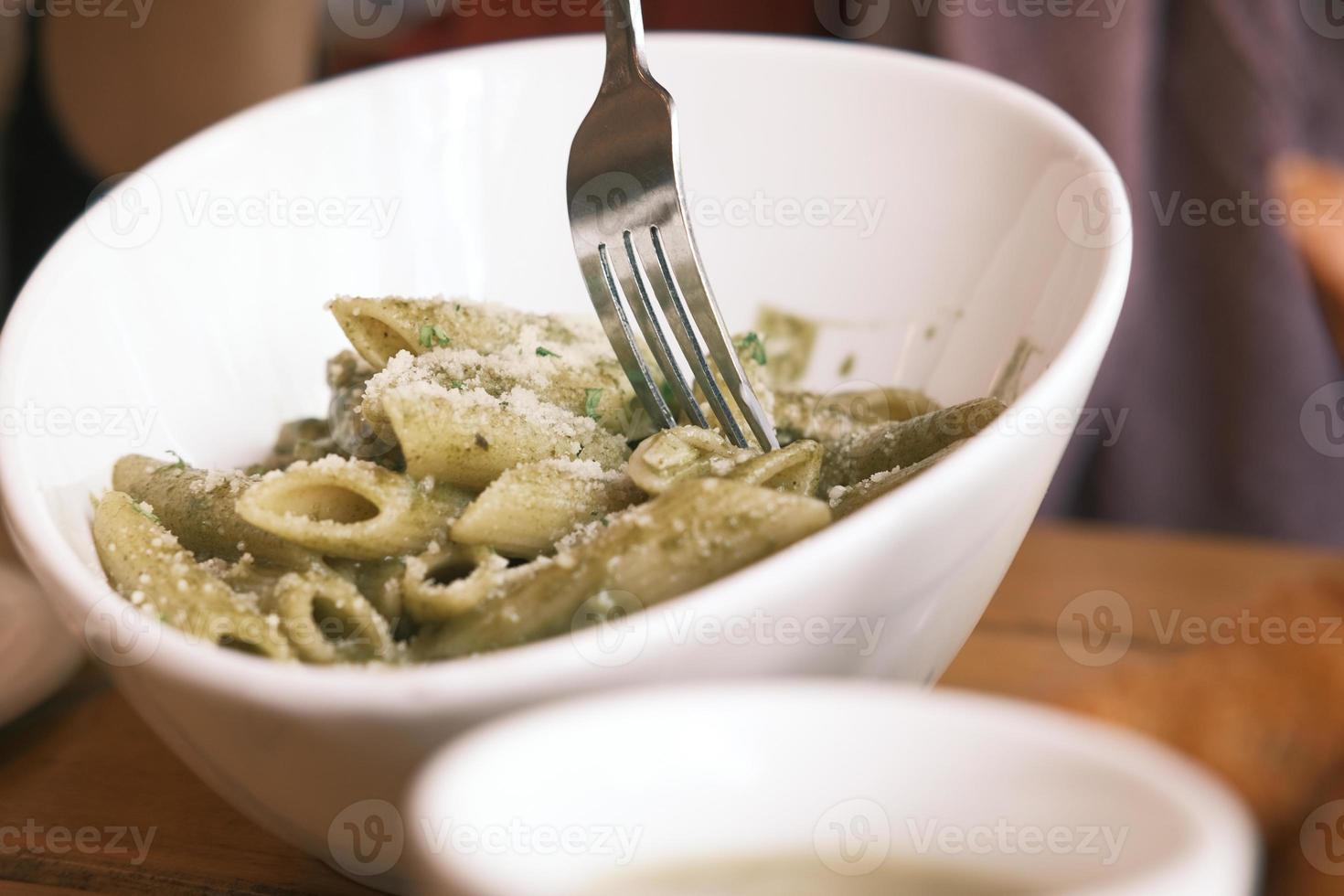 pasta med pesto i vit skål foto