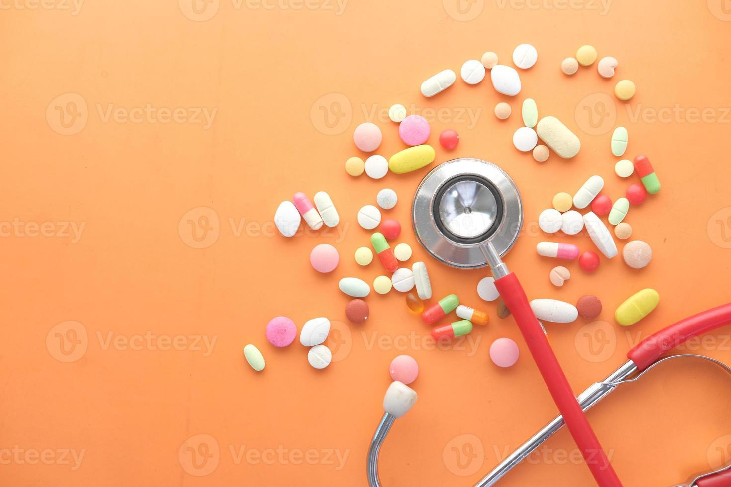 färgglada medicinska piller och stetoskop på orange bakgrund foto