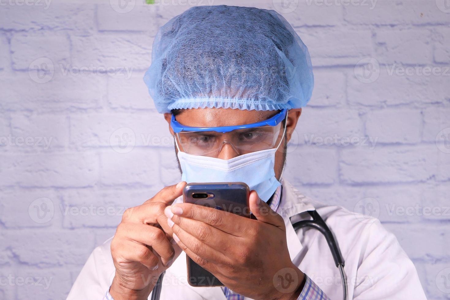 läkare i skyddsmask med smartphone på sjukhuset foto