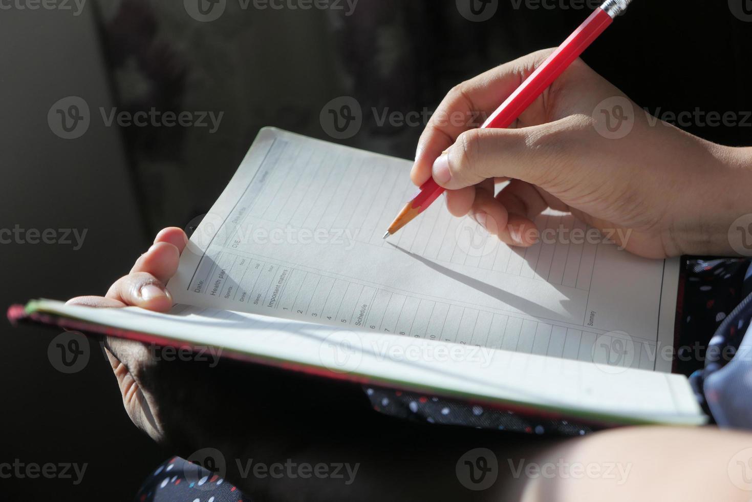person som skriver in i en dagbok foto