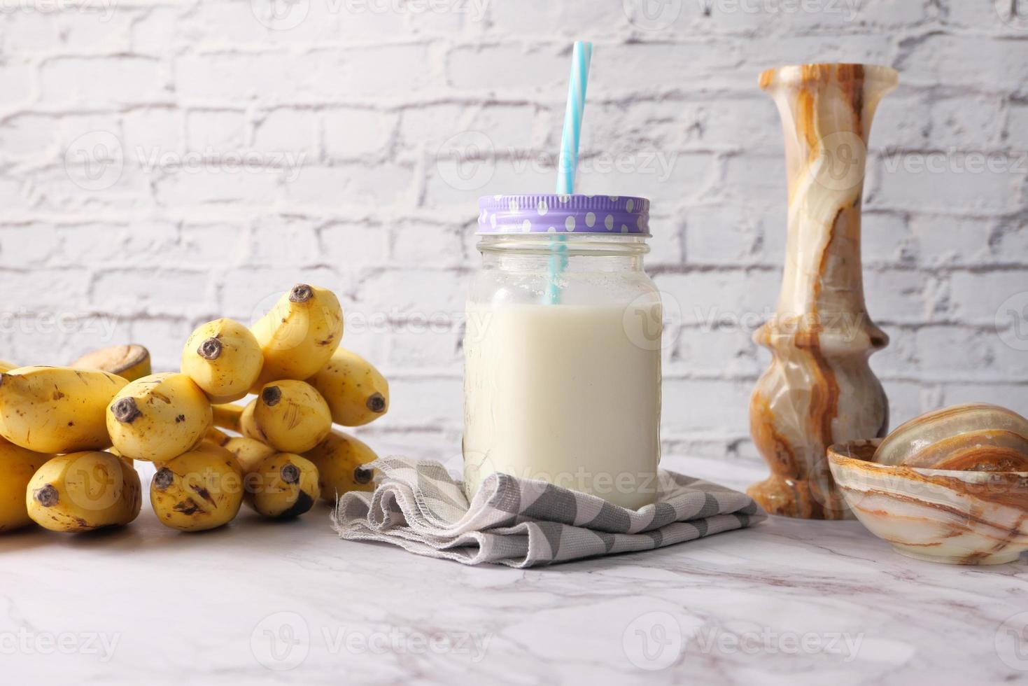 glas mjölk och bananer på bordet foto