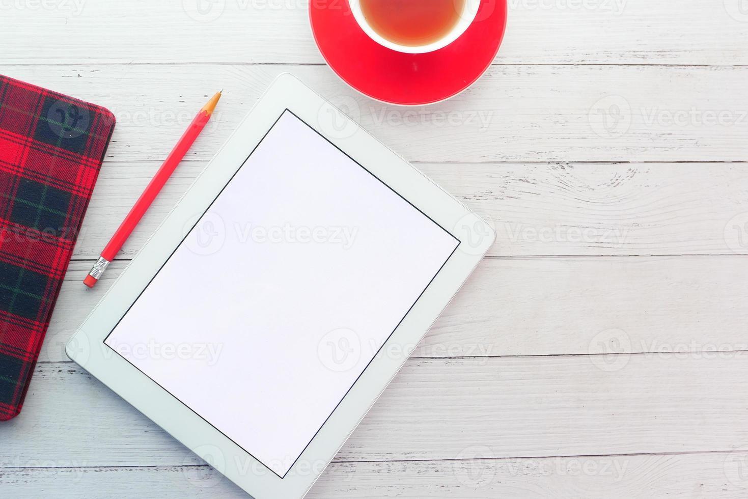 digital surfplatta med kontorsmateriel på bordet foto