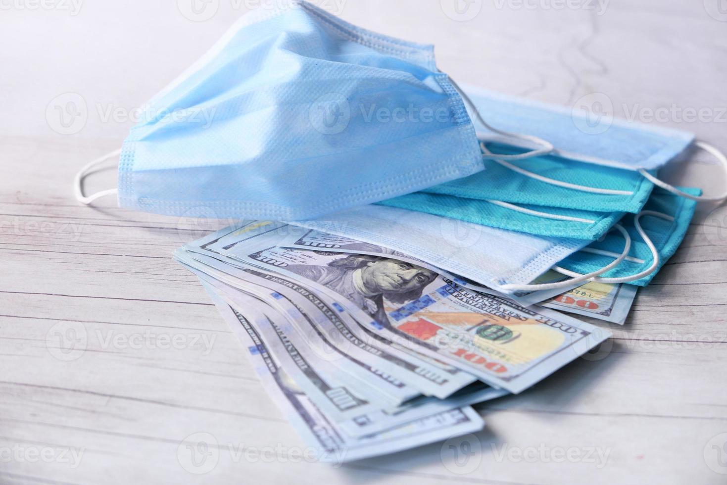 dollar och engångs ansiktsmasker på bordet foto