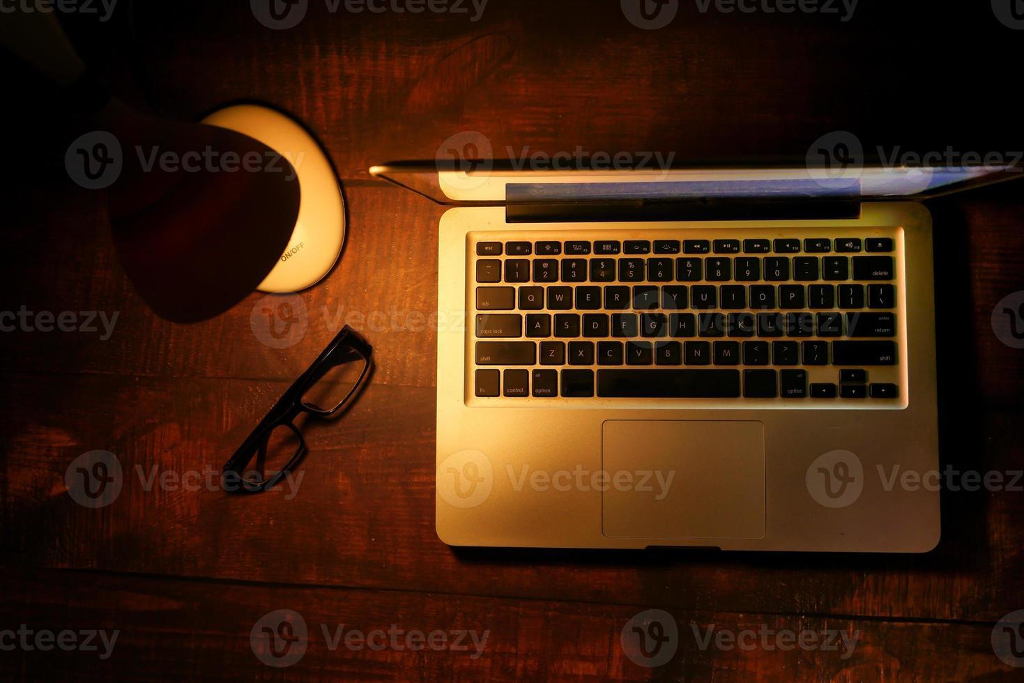 bärbar dator med bordslampa på skrivbordet foto