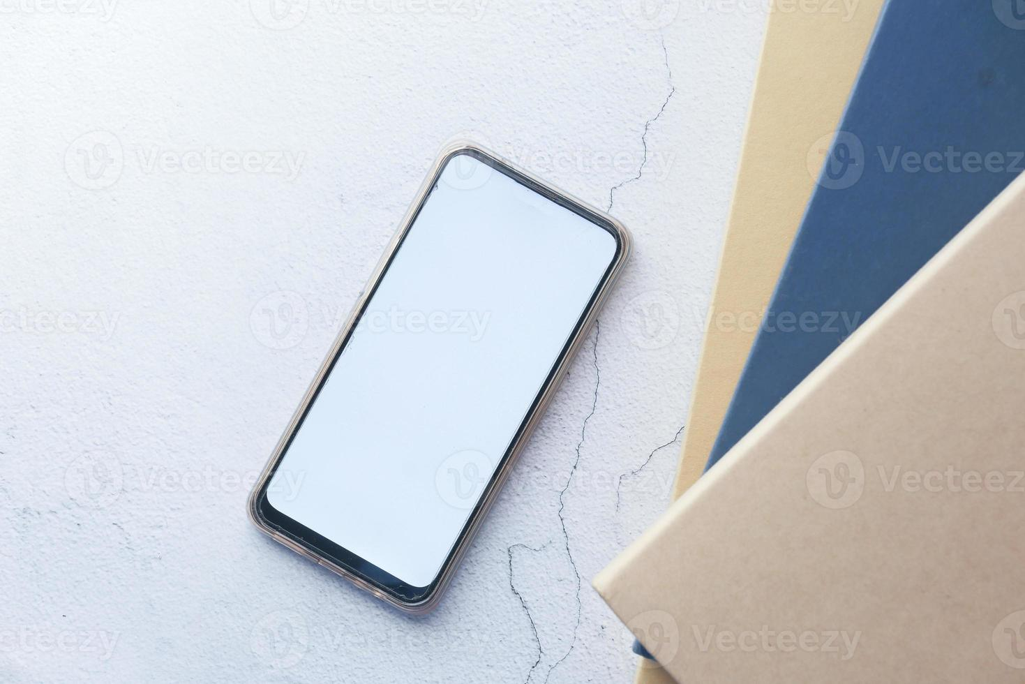 platt sammansättning av smart telefon och bunt med böcker foto