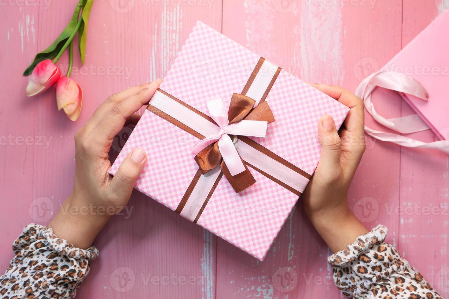 händer som håller rosa presentförpackning foto