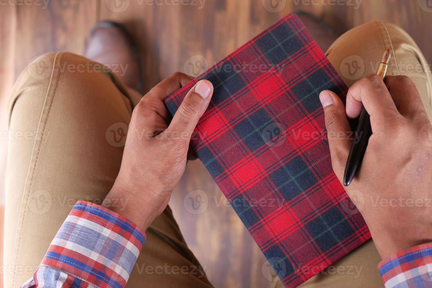 man håller anteckningsboken och penna foto