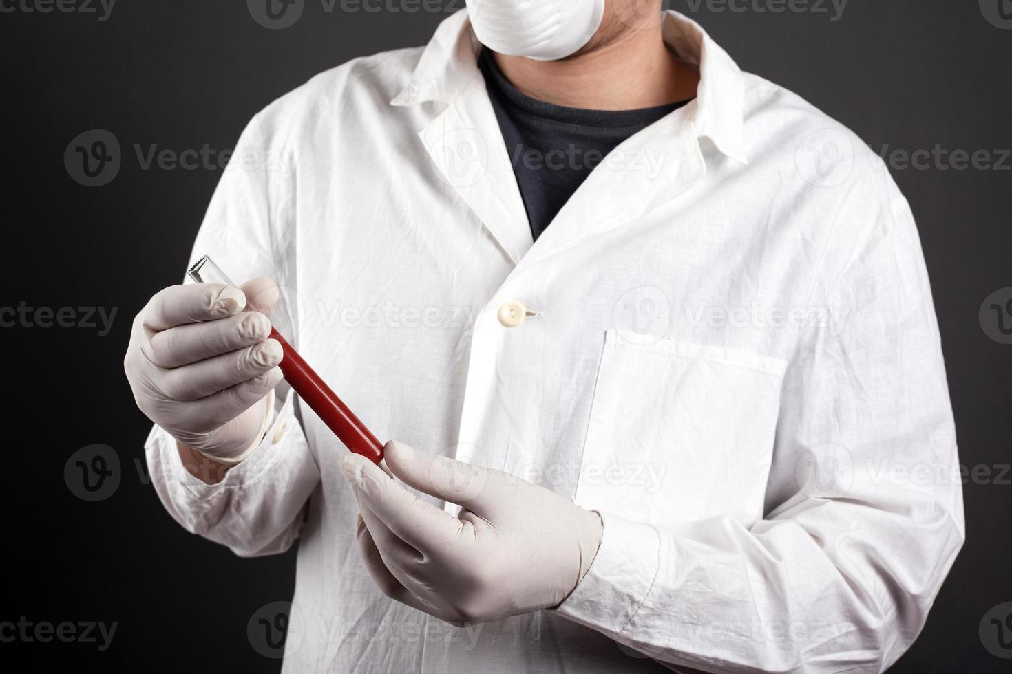 en läkare i medicinsk uniform håller ett provrör med blod i händerna foto