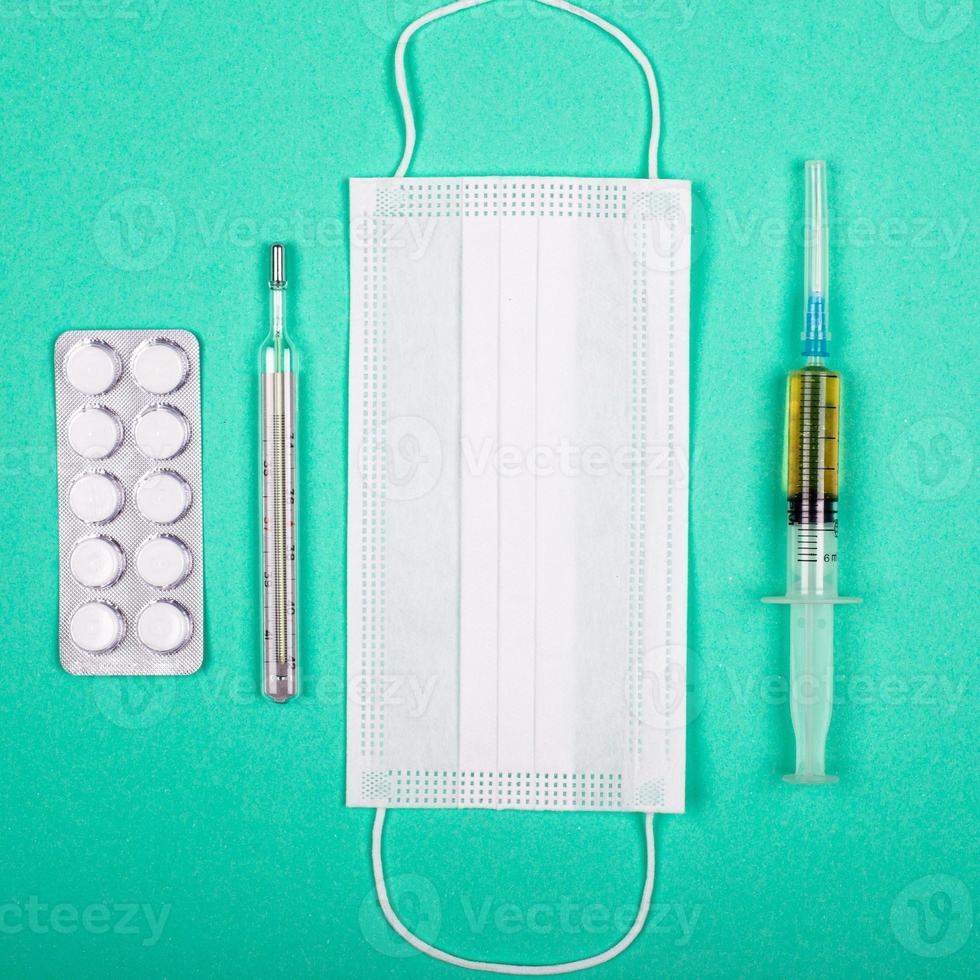 medicinska produkter för skydd mot koronaviruspandemi covid-19 på blågrön bakgrund foto