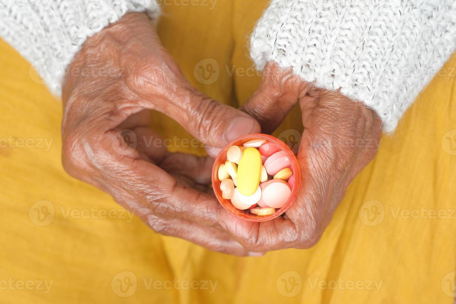 äldre kvinna som håller medicinsk pillerbehållare foto