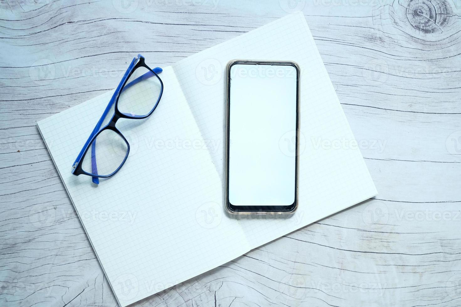 platt sammansättning av smart telefon och anteckningsblock på bordet foto