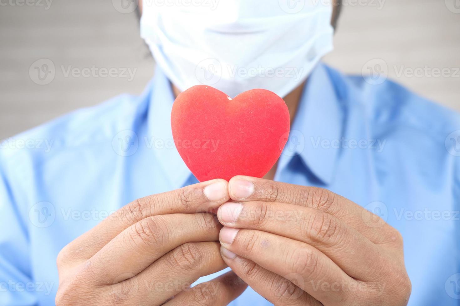 man i skyddande ansiktsmask som håller rött hjärta med kopieringsutrymme foto