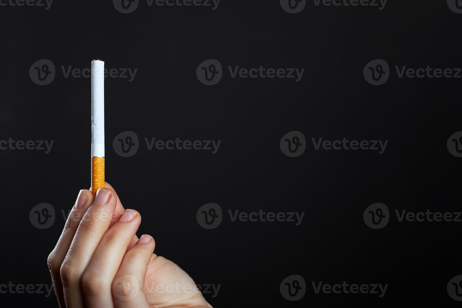 kvinnlig hand håller en cigarett på en mörk bakgrund foto