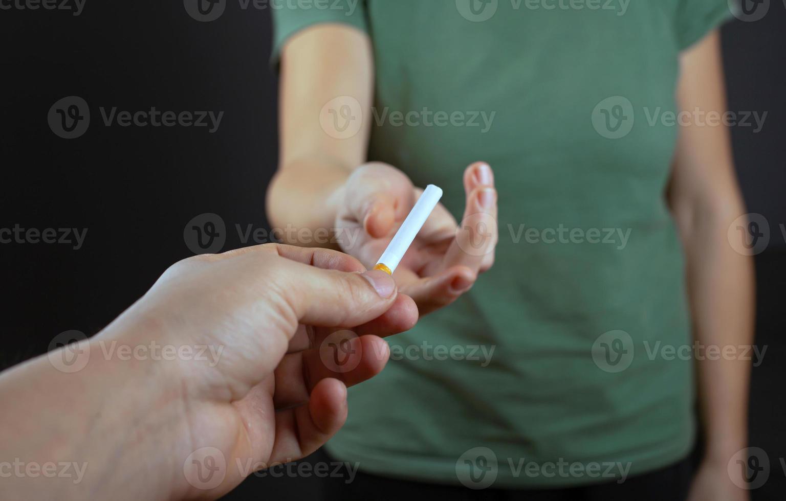 killen ger flickan en cigarett på en mörk bakgrund foto
