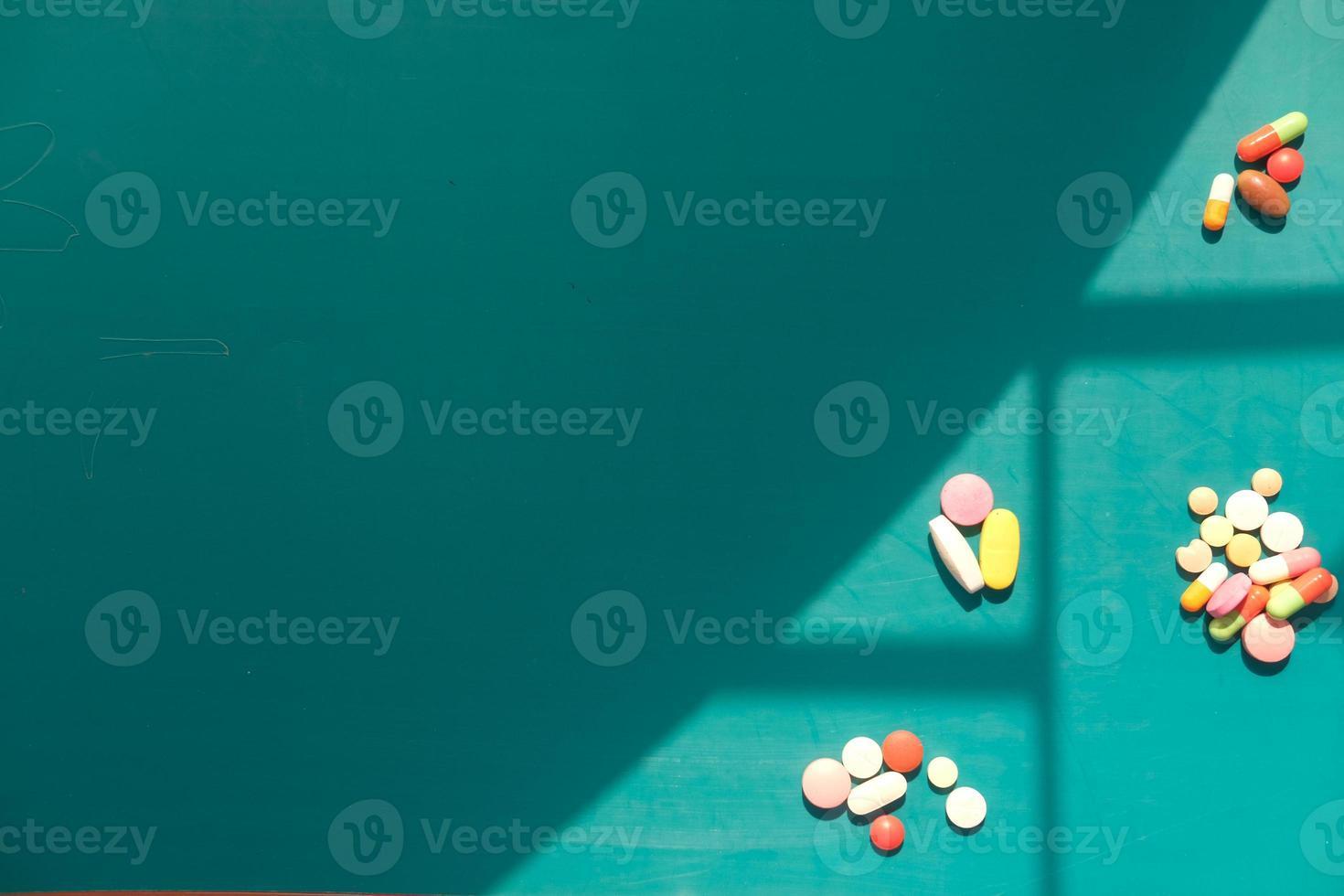 färgglada piller och kapslar på grön bakgrund foto