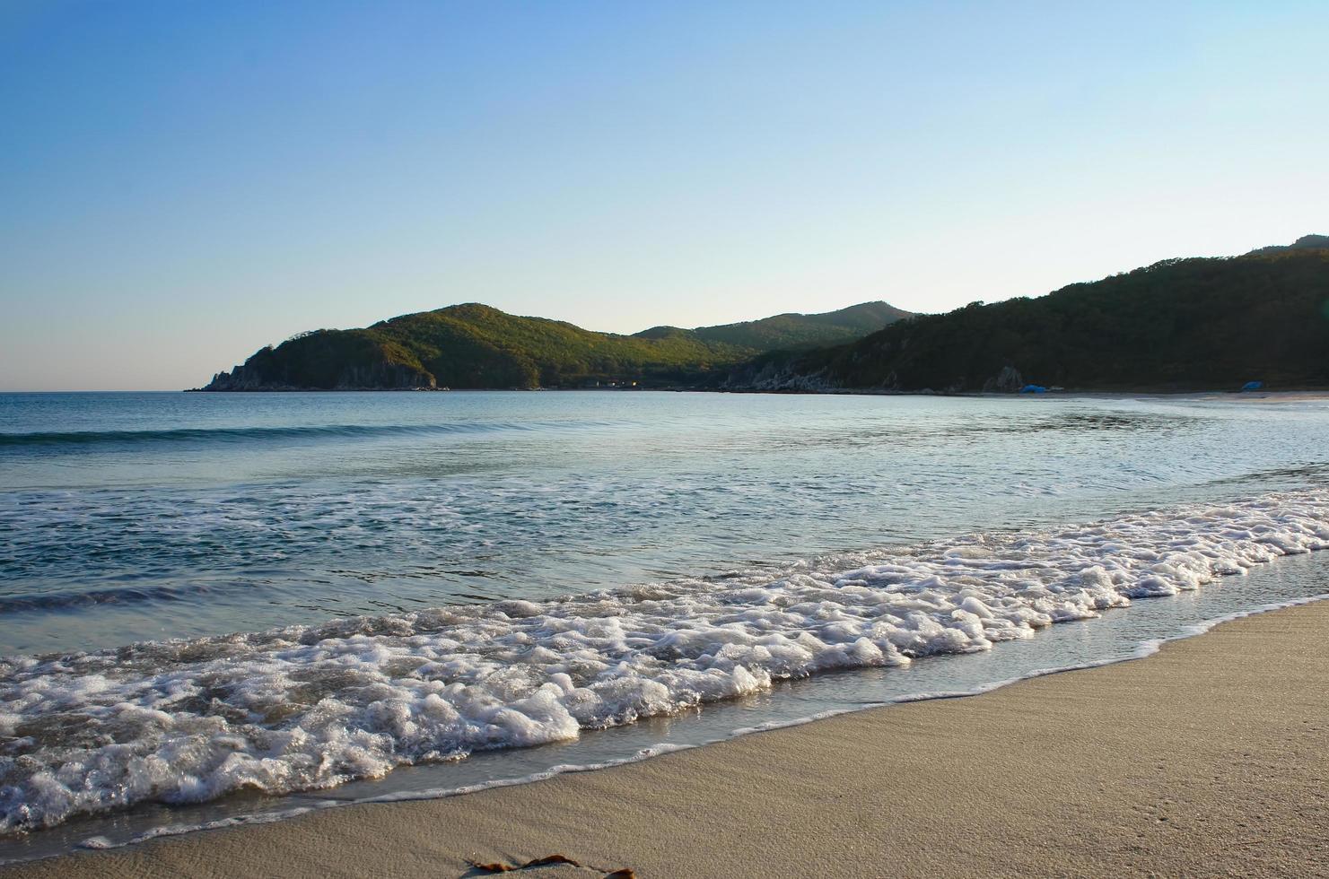 vågor vid stranden och bergen i bakgrunden vid Japans hav foto