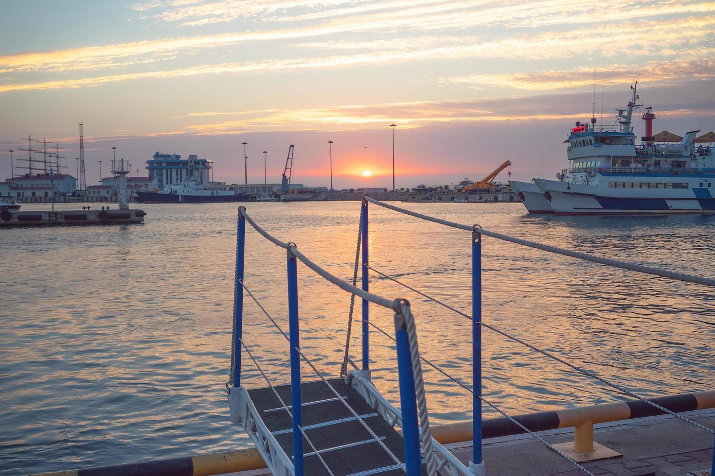 hamn med fartyg och en färgglad solnedgång i Sotji, Ryssland foto