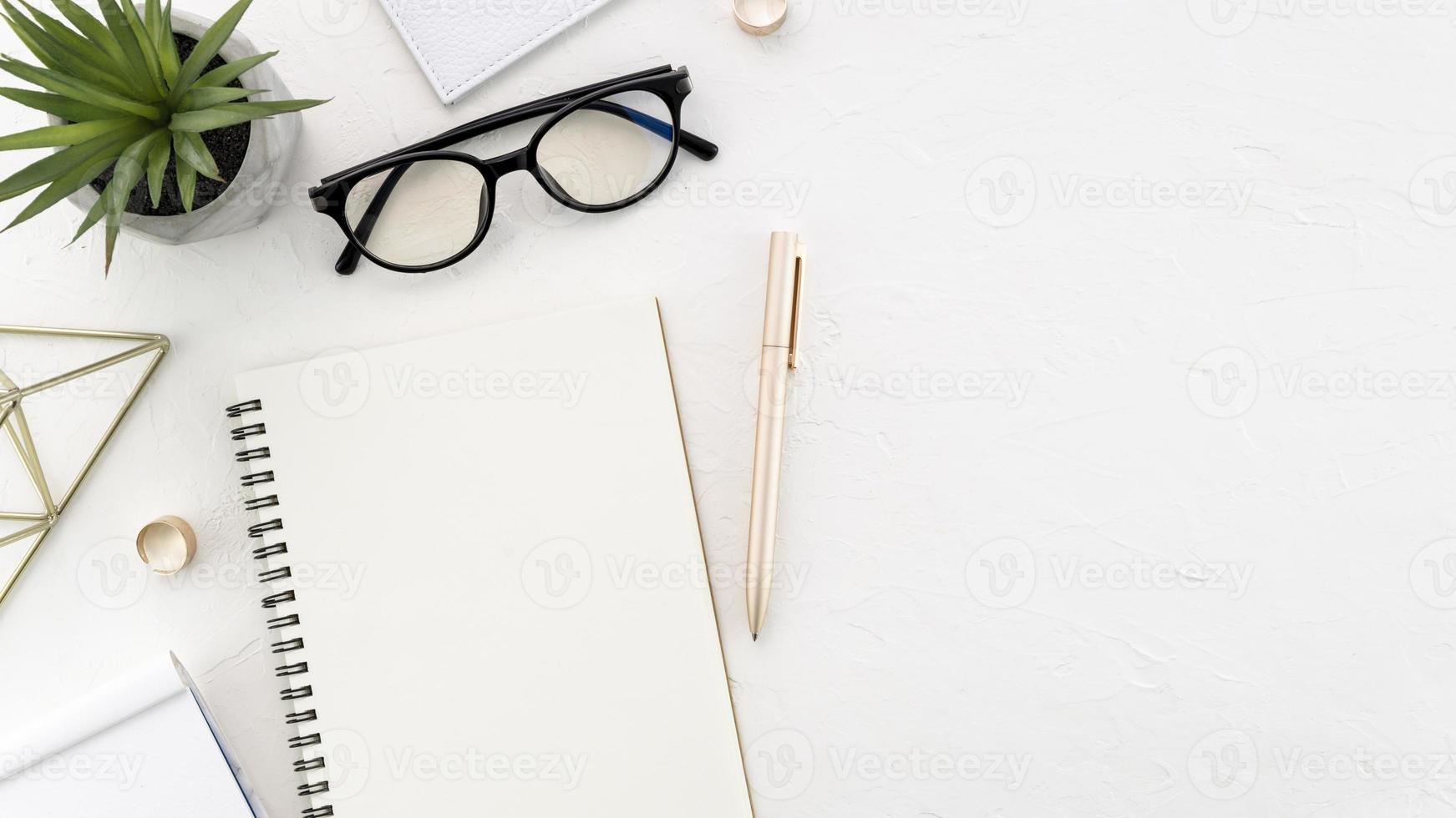 skrivbord med glasögon och anteckningsbok foto