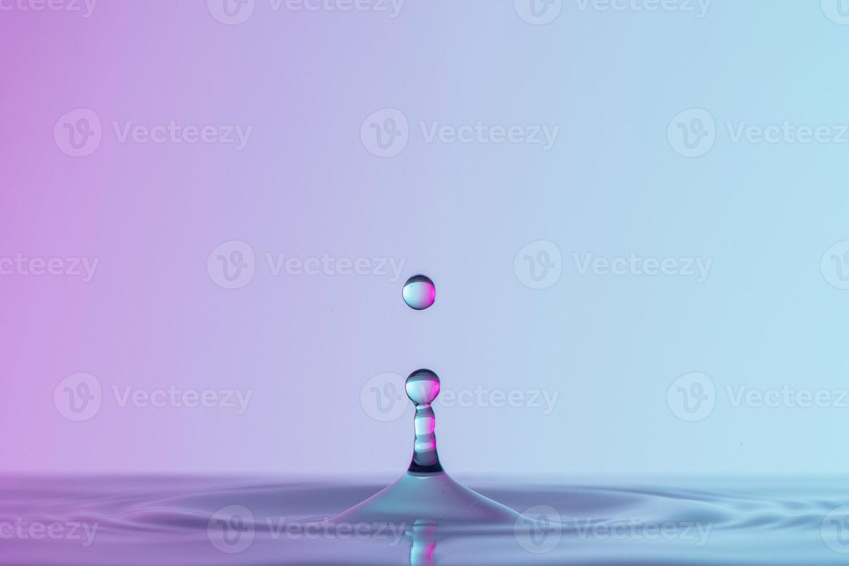 framifrån av droppar transparent vätska på rosa blå bakgrund foto