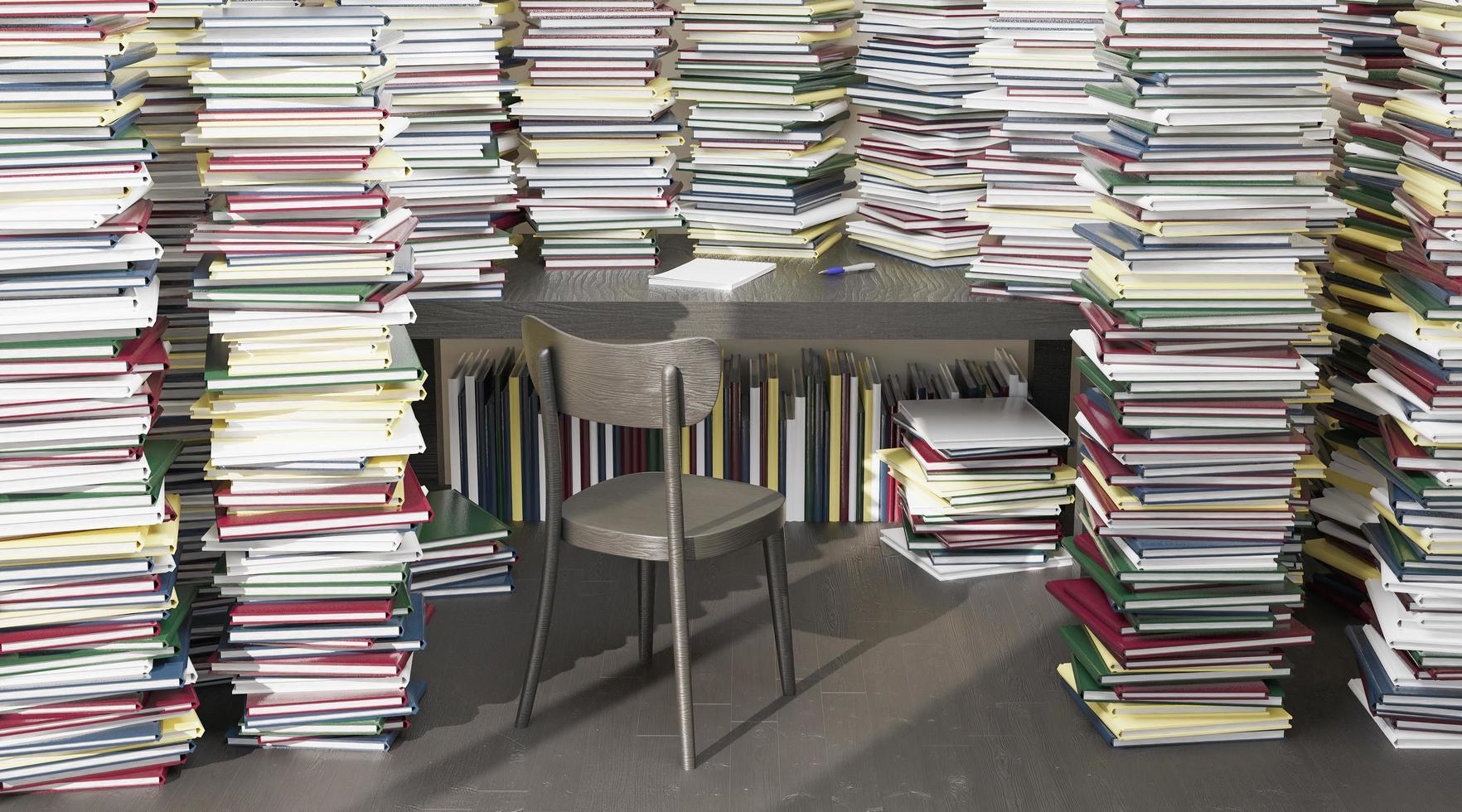 skrivbord omgivet av många böcker staplade runt foto